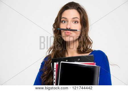 Amusing comical young woman holding folders and making funny face with pen over white background