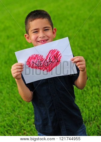 Child making choice to live a vegan lifestyle by holding a vegan and heart sign ** Note: Soft Focus at 100%, best at smaller sizes