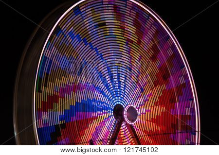 Round spinning wheel. Colorful lights blue pink, yellow, purple