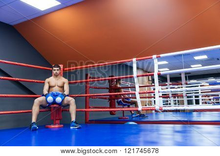 Male boxer sitting in the corner of the boxing ring and looking at camera