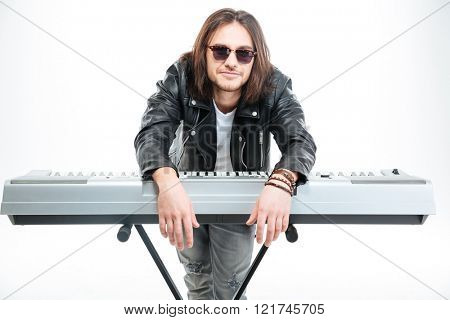 Handsome amusing young man standing and leaning on synthesizer over white background