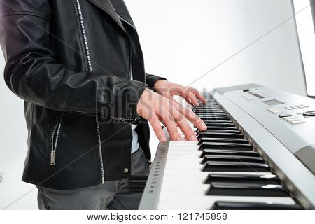 Closeup of hands of young man in black leather jacket standing and playing on synthesizer over white background