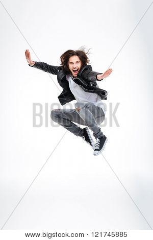 Handsome excited young man jumping and screaming over white background