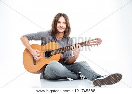 Smiling young man with long hair sitting on the floor and playing guitar over white background