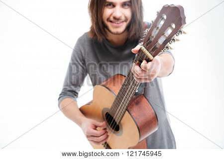 Attractive smiling young man with long hair playing acoustic guitar over white background