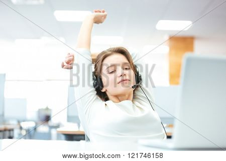 Relaxed beautiful young woman sitting and stretching on workplace in office