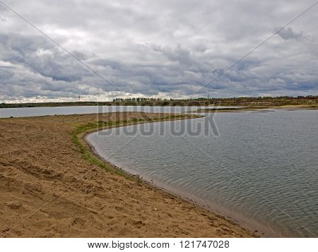Sandy beach on the lake in stormy weather