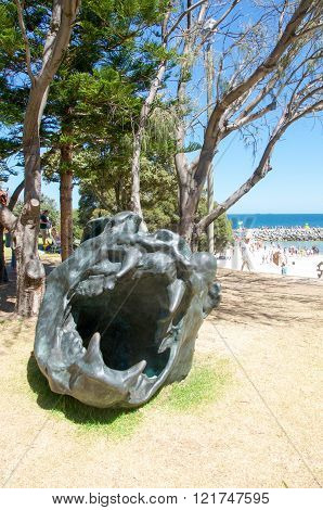 COTTESLOE,WA,AUSTRALIA-MARCH 12,2016: Dark creature sculpture with tourists at the