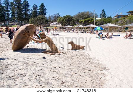 COTTESLOE,WA,AUSTRALIA-MARCH 12,2016:  Stone human figure and dog sculpture with tourists at the