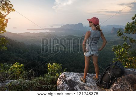 Young woman hiker relaxing on the mountain and watching sunset over the valley