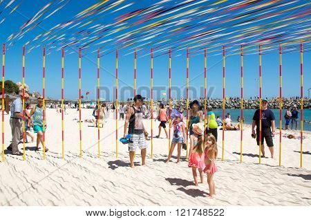 COTTESLOE,WA,AUSTRALIA-MARCH 12,2016:  Interactive ribbon and pole sculpture with people at the public arts festival