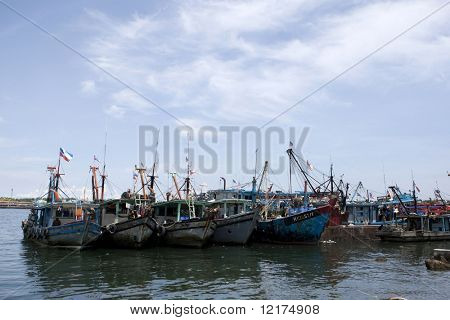 LABUAN - JULY 16: Fishing boats and trawlers moor at the jetty after returning from sea. July 16, 2010 Labuan, Borneo. The fishing industry contributes a significant income to islanders here.