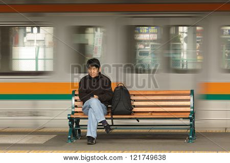 FUJI CITY, JAPAN, NOVEMBER 23, 2011 : A man is sitting on a bench with the motion of a train behind him in the train station of Fuji City, Japan