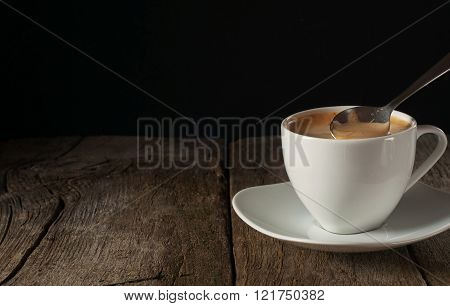 Cup of coffee closeup with thick of crema on wooden table on black background. Coffee background