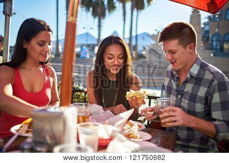group of friends eating meal together at outdoor restaurant