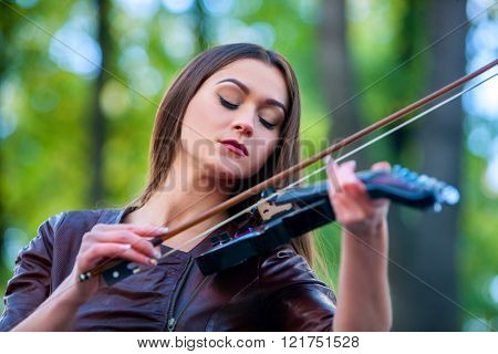 Music street performers girl violinist  playing  in spring park outdoor. Violin music nature.