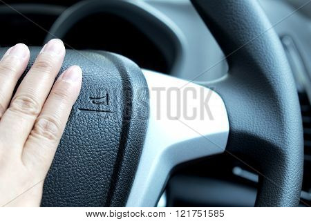 Driving/steering wheel with horn sign and hand near sign. Focus on horn sign.