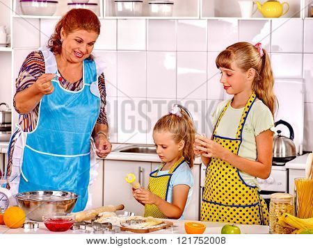 Grandmother and granddaughter baking cookies. Cooking at kitchen.