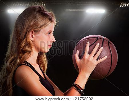 Woman throwing basketball in gym.