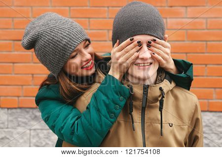 Couple in love. Young Women close men eyes by hands. Brick background