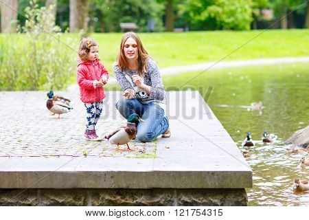 Mother and her children feeding ducks at summer