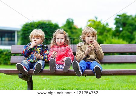 Three siblings sitting on bench and eating chocolate. Two littlke kid boys and girl having fun. Siblings and family