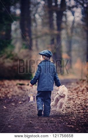 Cute Little Child, Holding Lantern And Teddy Bear In Forest