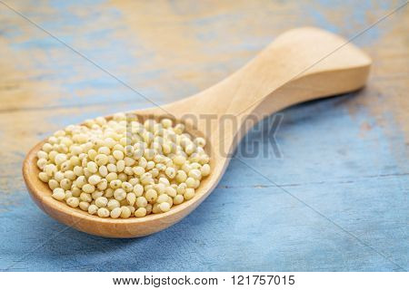 millet grain on a wooden spoon against blue painted grunge wood