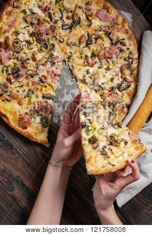 Hand Taking Single Slice Of Italian Pizza
