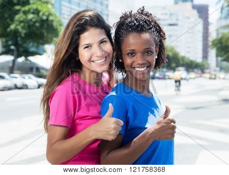 Two African And Caucasian Women Showing Thumb In The City