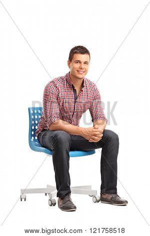 Vertical shot of a young cheerful man sitting on a blue chair isolated on white background