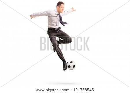 Studio shot of young businessman playing football shot in mid-air isolated on white background