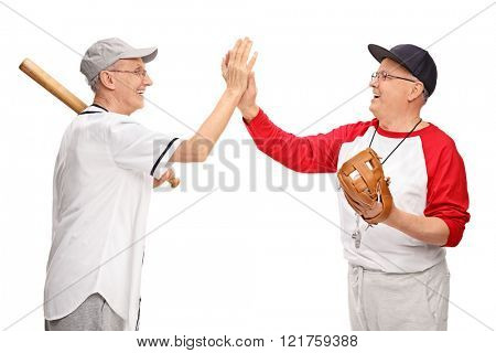 Studio shot of two senior men in baseball outfits high-five each other isolated on white background