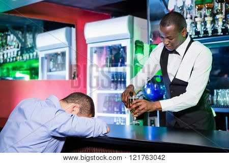Drunk man sleeping with his head on bar counter while bartender making a drink for him