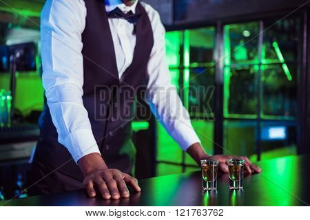Two glasses of tequila on bar counter and bartender leaning in background