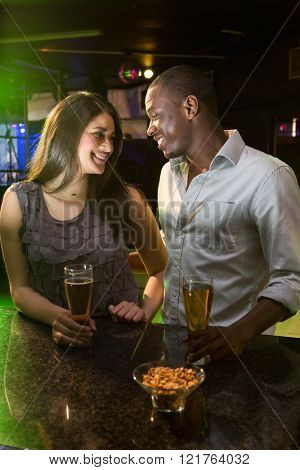 Couple looking at each other while having beer at bar counter in bar