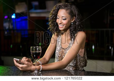 Beautiful woman typing a text message while having wine at bar counter