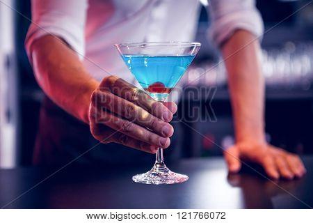Bartender serving a blue martini in bar