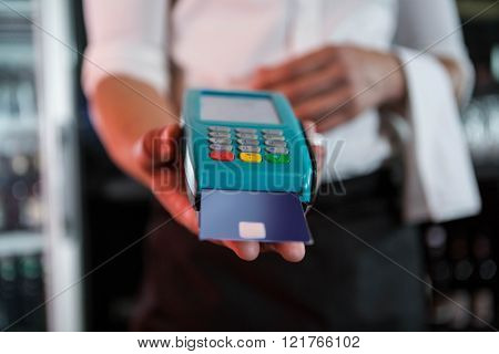 Bartender accepting a credit card at bar counter in bar