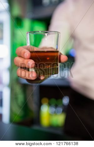Bartender serving a glass of whiskey in bar