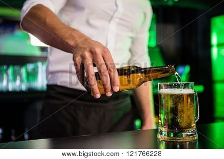 Mid section of bartender pouring beer in a glass at bar counter