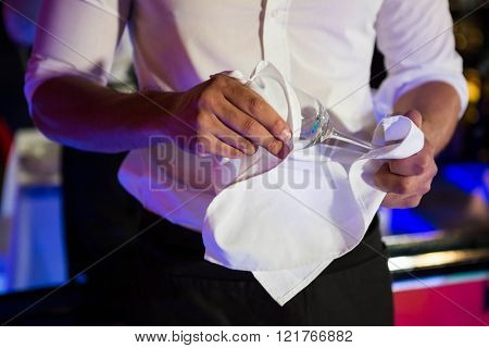Barkeeper wiping a wine glass with napkin