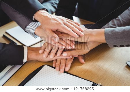 Close-up of businesspeople stacking hands in conference room