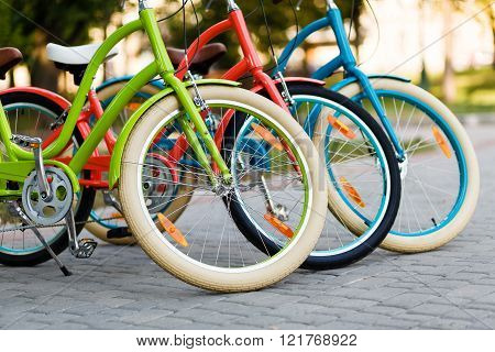 Bright city bikes. City bicycles. Bicycles wheels. Three beautiful lady city bright colored bicycles or bikes for woman standing in the summer park outdoors, wheel closeup.