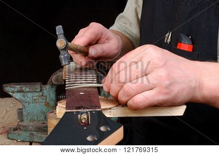 Luthier establishes frets in a signature stamp of an electric guitar replacement of frets on new.