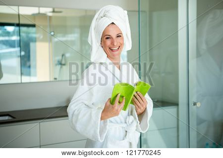 woman in a dressing gown reading a book in the bathroom