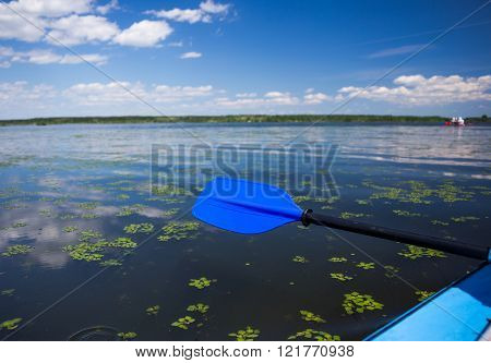Blue paddle lying on kayak. Kayaking on a river
