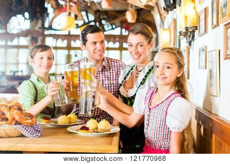 Bavarian girl wearing dirndl and eating with family in traditional restaurant