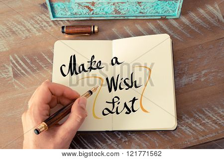 Retro effect and toned image of a woman hand writing a note with a fountain pen on a notebook. Handwritten text Make A Wish List as business concept image