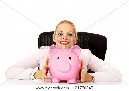 Happy business woman with a piggy bank behind the desk